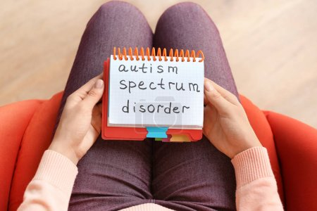 "Photo for Woman holding notebook with phrase ""Autism spectrum disorder"" on knees, closeup - Royalty Free Image"
