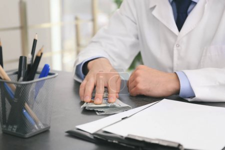 Doctor with bribe at workplace