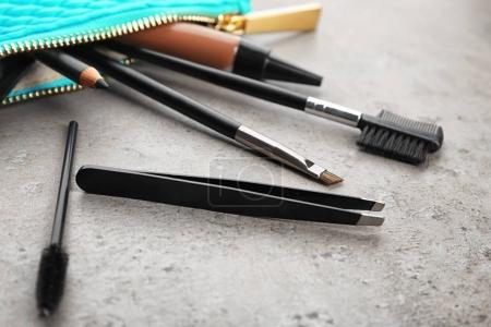 Set of tools for eyebrow dyeing and correction on grey background