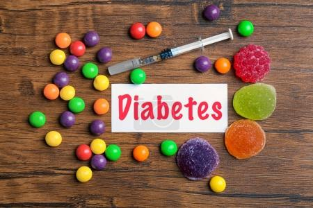"""Composition with word """"Diabetes"""", sweets and syringe on wooden background"""
