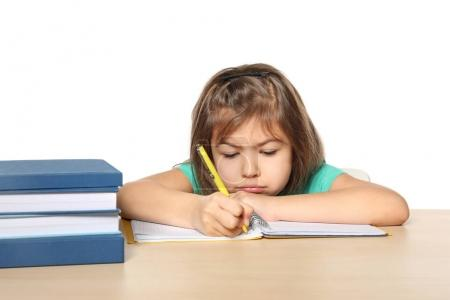 Cute little girl doing homework against white background