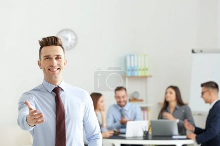 Young businessman offering handshake in conference room
