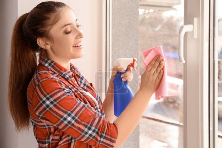 Young woman cleaning window indoors