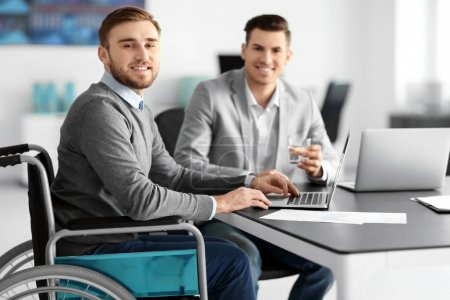 Young man in wheelchair with colleague at workplace