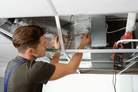 Photo pour Homme technicien réparation climatiseur industriel à l'intérieur - image libre de droit