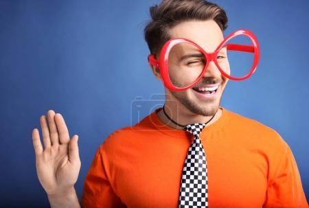 Young man in funny glasses on color background. Ap...