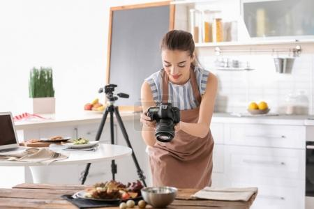 Foto de Mujer joven con cámara profesional tomar fotografías de naturaleza muerta en la cocina - Imagen libre de derechos