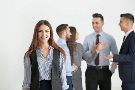 Young smiling businesswoman and her team on light background