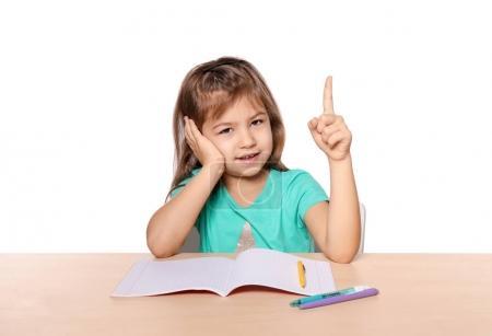 Jolie petite fille avec le doigt index levé sur fond blanc. Enfant fait ses devoirs