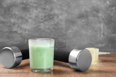 Glass with protein shake and dumbbells on table