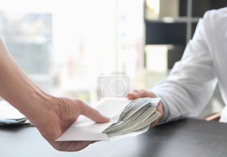 Doctor receiving bribe from patient at workplace