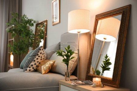Elegant room interior with mirror on nightstand