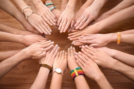 People putting hands together at wooden table as symbol of unity