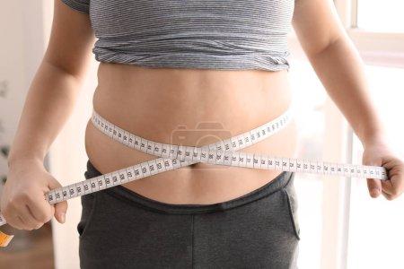 Overweight boy measuring waist