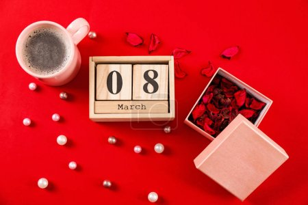Photo for Wooden block calendar, flower petals and cup of coffee on color background. International Women's Day celebration - Royalty Free Image