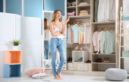 Photo pour Jeune femme choisir des vêtements dans la garde-robe à la maison - image libre de droit