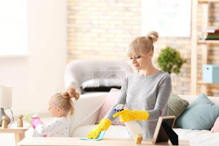 kleines Mädchen und ihre Mutter beim Aufräumen zu Hause