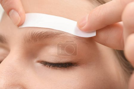 Young woman undergoing eyebrow correction procedure, closeup