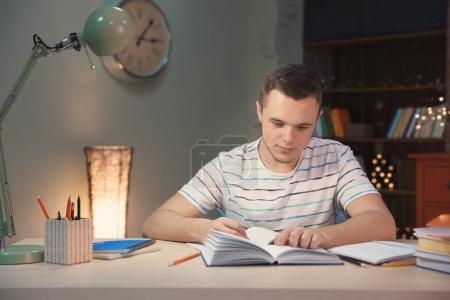 Photo pour Étudiant faisant ses devoirs à l'intérieur tard dans la nuit - image libre de droit