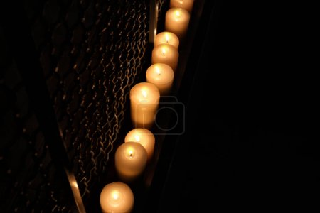 Many burning candles in darkness