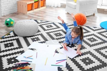 Little girl drawing on floor at home