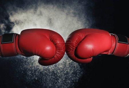 Photo pour Hommes en gants de boxe sur fond noir - image libre de droit