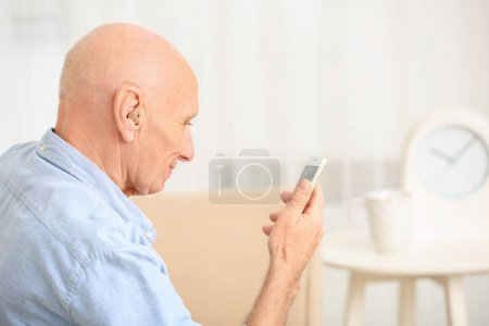 Hearing impaired man with phone at home