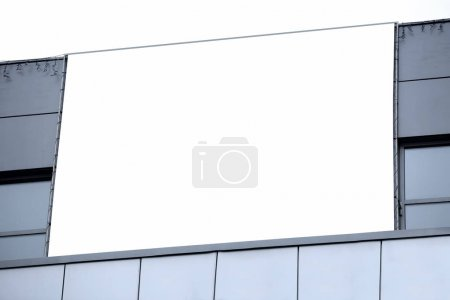 Blank advertising board on city building outdoors