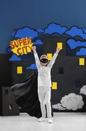 Cute boy as superhero against decoration. Comic strip city theme