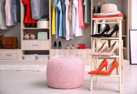 Photo for Pink ottoman chair and stand with shoes in dressing room - Royalty Free Image