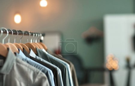 Photo for Clothes rack with many shirts indoors, closeup. Fashionable wardrobe - Royalty Free Image