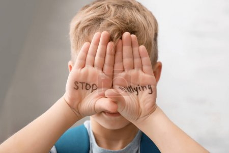 "Little boy with words ""Stop bullying"" on light background"