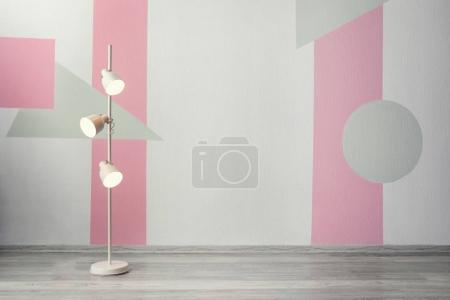 Stylish floor lamp near color wall