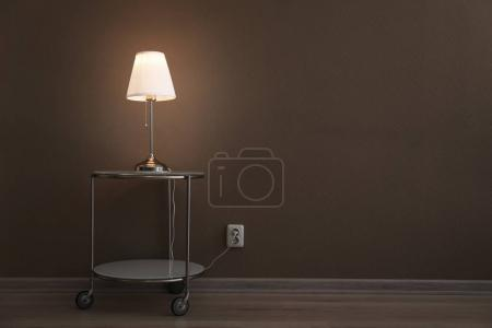Photo for Stylish table lamp near wall - Royalty Free Image
