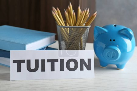 Photo for Paper with word TUITION and piggy bank on table - Royalty Free Image