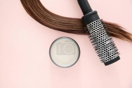 Photo pour Bocal avec de l'argile pour le coiffage, brosse et mèche de cheveux brun sur fond de couleur - image libre de droit