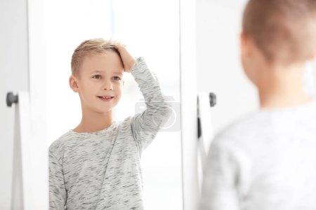 Cute little boy looking at himself in mirror indoors