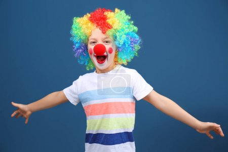 Cute little boy with clown makeup in rainbow wig on color background. April fool's day celebration