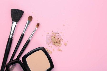 Photo pour Poudre faciale et pinceaux de maquilleur professionnel sur fond de couleur - image libre de droit
