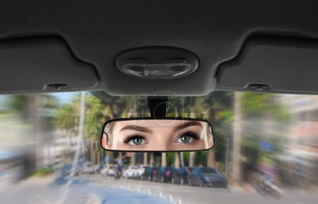 Reflection of young woman in car rear view mirror