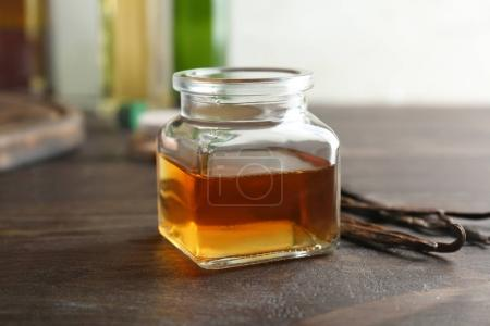 Jar with vanilla extract and sticks
