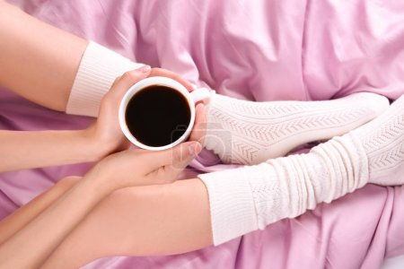Young woman in socks with cup of coffee on bed