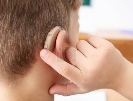 Little boy turning on hearing aid, closeup