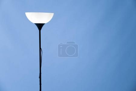 Stylish lamp on color background
