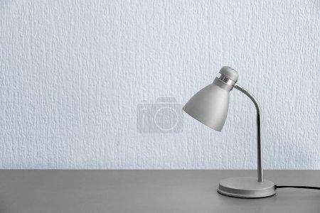 Photo pour Lampe de table élégante près du mur blanc - image libre de droit