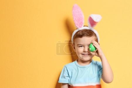 Photo pour Mignon petit garçon avec des oreilles de lapin tenant oeuf de Pâques sur fond de couleur - image libre de droit