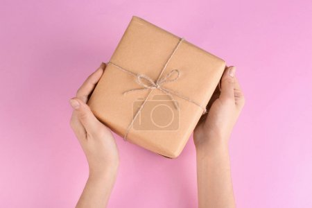 Woman holding parcel on color background