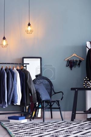 Dressing room interior with clothes on rack. Fashionable wardrobe