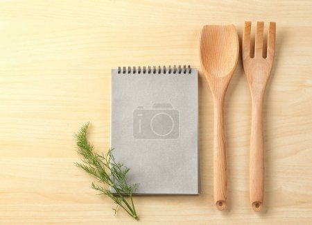 Photo for Notebook and kitchen utensils on wooden background. Cooking master classes - Royalty Free Image