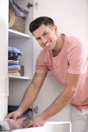 Photo for Man picking outfit from closet. Fashionable wardrobe - Royalty Free Image